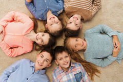 Happy smiling children lying on floor in circle Royalty Free Stock Photo