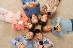 Happy smiling children lying on floor in circle Royalty Free Stock Images