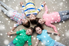 Happy smiling children lying on floor over snow Stock Photography