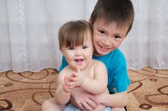 Happy smiling children portrait. Siblings - boy holding little baby girl, together sitting home Stock Photos
