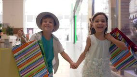 Happy smiling children with shopping bags in hands running through mall after buy in expensive boutiques. On black Friday stock video footage