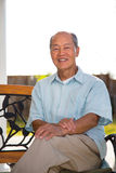 Happy Smiling Chinese Senior Sitting at Backyard Stock Images