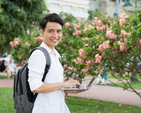 Happy smiling college student with laptop. Isolated on nature background Royalty Free Stock Photos