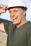 Happy smiling construction worker. A handsome smiling construction worker wearing a hard hat is smiling Royalty Free Stock Photography