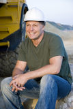 Happy smiling construction worker. A handsome smiling construction worker wearing a hard hat is sitting on a rock next to his digger and taking a break Royalty Free Stock Photos