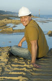 Happy smiling construction worker. A happy smiling construction worker wearing a hard hat and sitting on the sand taking a break from work Royalty Free Stock Photography