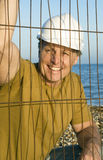 Happy smiling construction worker. A happy smiling construction worker looking through a wire fence and wearing a white hard hat Royalty Free Stock Image