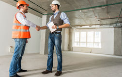 Happy smiling contractors meeting in apartment. Hilarious builders are shaking hands and looking at each other with smile. Foreman holding tablet. Low angle royalty free stock photos