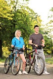 Happy smiling couple with bikes posing Royalty Free Stock Photos