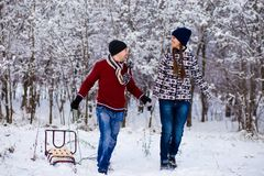 Happy smiling couple in bright clothes have fun in winter snow park. With sleigh Stock Photo