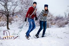Happy smiling couple in bright clothes have fun in winter snow park. With sleigh Royalty Free Stock Image
