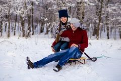 Happy smiling couple in bright clothes playing in winter. Snow park on sleigh Royalty Free Stock Photography