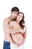 Happy smiling couple embracing with pregnant belly Stock Photos