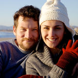 Happy smiling couple in front of beach looking camera during sunset Stock Photography