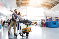 Happy smiling couple having fun at airport. I believe I can fly. Cheerful women is sitting on baggage and men pulling cart forward. They looking ahead with royalty free stock image