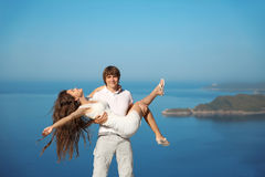 Happy smiling couple having fun over blue sky background. Enjoym. Ent. holidays, vacation, love and happiness concept Royalty Free Stock Photos