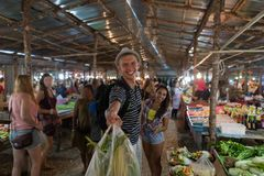 Happy Smiling Couple Hold Bags With Vegetables In Street Market Cheerful Man And Woman Shopping Together On Exotic Stock Image