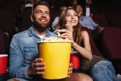 Happy smiling couple holding a big popcorn bucket Royalty Free Stock Photos