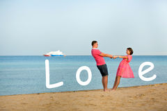 Happy young smiling couple holding hands on the beach. The inscription Love. Royalty Free Stock Image