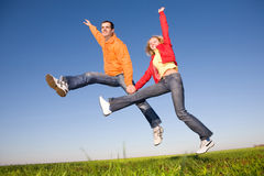 Happy smiling couple  jumping in blue sky Royalty Free Stock Image
