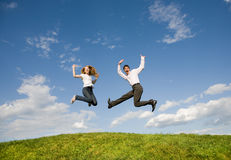 Happy smiling couple  jumping in blue sky Stock Photos