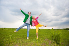 Happy smiling couple  jumping in the field Stock Photo