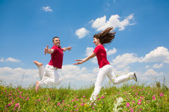 Happy smiling couple  jumping in sky Stock Images