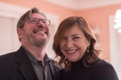 Middle aged couple laughing at party. Happy smiling couple laughing and having fun at friends party royalty free stock images