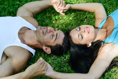 Happy smiling couple laying on green grass Royalty Free Stock Image