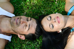 Happy smiling couple laying on green grass stock images
