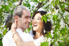 Happy smiling couple in love in bloomy garden Royalty Free Stock Photos