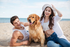 Happy smiling couple in love sitting on beach with dog Royalty Free Stock Photos