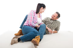 Happy smiling couple in love sitting on the floor Stock Images