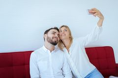 Happy and smiling couple lovely is making selfie with mobile phone together in living room at home. Happy and smiling couple lovely is making selfie with mobile royalty free stock photography