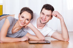 Happy smiling couple. A happy smiling couple lying on the floor with a tablet stock photo