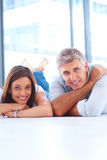 Happy smiling couple lying on white floor Stock Photography