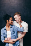 Happy smiling couple. Man and woman, love and care. Happy and young smiling interracial couple on dark background. Black women and white man, family love and Stock Photo