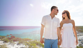 Happy smiling couple over summer beach and sea stock photography