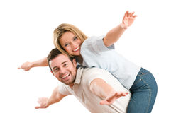 Happy smiling couple piggyback arms outstretched Stock Photos