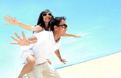 Happy smiling couple piggyback together with arms outstretched. At beautiful beach Royalty Free Stock Image