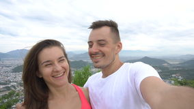 Happy smiling couple recording video, taking selfie in the mountains with aerial city view. Man kisses girl stock footage
