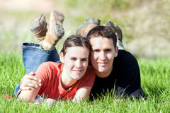 Happy smiling couple relaxing. Happy smiling couple relaxing on green grass Royalty Free Stock Photography