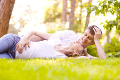 Happy Smiling Couple Relaxing on Green Grass Royalty Free Stock Photography