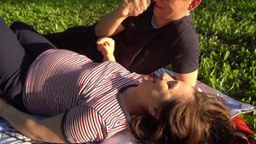 Happy smiling couple relaxing on green grass. Park.Young family lying on grass outdoors. stock video footage