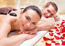 Happy smiling couple relaxing in spa salon. Portrait of happy smiling couple relaxing in spa salon with hot stones on body stock photography