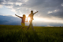 Happy smiling couple run on the field Stock Photography