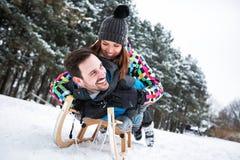 Happy smiling couple sledding. Through big beautiful montain Stock Photos