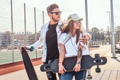 Happy smiling couple is standing on the summer street with their longboards stock photo