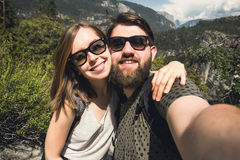 Happy smiling couple of students in love take selfie self-portrait while hiking in Yosemite National Park, California. Happy smiling couple in love take selfie Royalty Free Stock Photography
