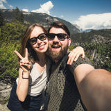 Happy smiling couple of students in love take selfie self-portrait while hiking in Yosemite National Park, California. Happy smiling couple in love take selfie Stock Photography